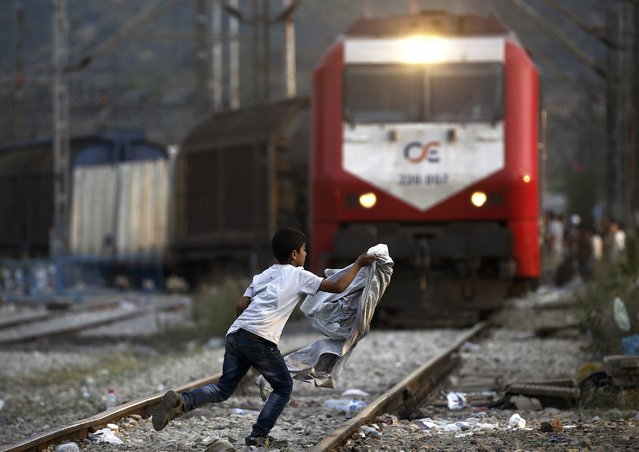 A Syrian refugee boy runs across rail tracks as a freight train approaches near Greece's border with Macedonia, outside the Greek village of Idomeni, September 7, 2015. (Photo by Yannis Behrakis/Reuters)