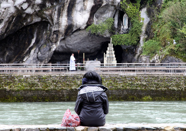 A pilgrim prays in front of the Roman Catholic shrine at Lourdes, in southwestern France, Saturday, May 16, 2020, after being closed on March 17 for the first time in its history following the coronavirus pandemic. The COVID-19 pandemic emptied out churches and also forced the cancellation of the Lourdes pilgrimage. (Photo by Bob Edme/AP Photo)