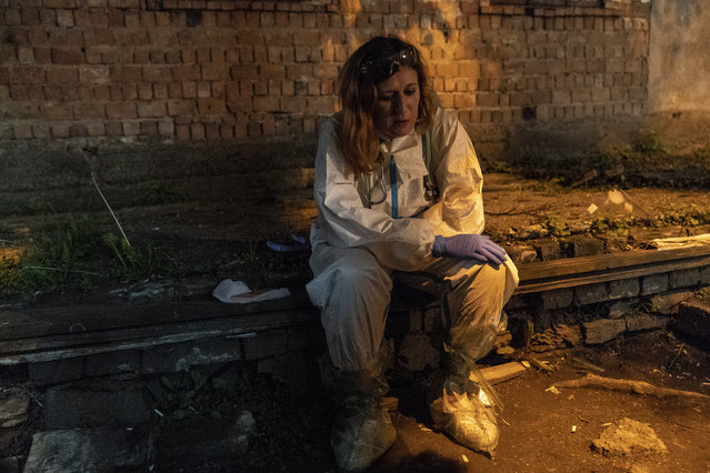 In this photo taken on Saturday, May 9, 2020, Dr. Dr Olha Kobevko takes a quick break outside the regional hospital in Chernivtsi, Ukraine. The hospital lacks a centralized oxygen supply and has to rely mostly on refillable oxygen masks, reflecting a pitiful state of Ukraine's underfunded health care system that was quickly overwhelmed by the coronavirus even with a relatively low number of infections. (Photo by Evgeniy Maloletka/AP Photo)