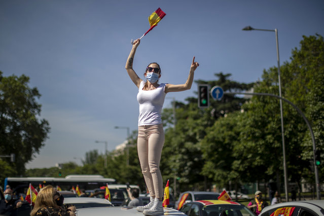 A woman waves a Spanish flag during a drive-in protest organised by Spain's far-right party Vox against the Spanish government's handling of the nation's coronavirus outbreak in Madrid, Spain Saturday, May 23, 2020. (Photo by Manu Fernandez/AP Photo)