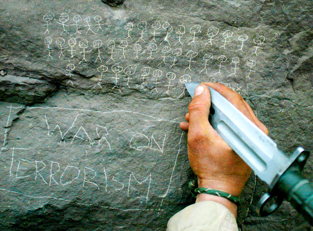 A U.S. Army 10th Mountain Division soldier from Miami, Florida carves the body count that their mortar team has chalked up on a rock, near the villages of Sherkhankheyl, Marzak and Bobelkiel, March 9, 2002. (Photo by Joe Raedle/Reuters)