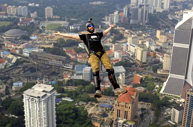 BASE jumper Luke Denniss of Australia gestures as he dives in the air from the Kuala Lumpur Tower during the KL Tower International Jump in Kuala Lumpur, Malaysia, Saturday, September 27, 2014. BASE stands for the places such jumpers usually jump from: buildings, antennas, spans (bridges) and earth (cliffs). (Photo by Lai Seng Sin/AP Photo)