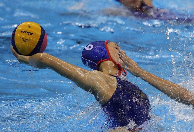 Russia's Olga Gorbunova,passes the ball forward as Hungary's Dora Czigany, goes to block during their women's bronze medal water polo match at the 2016 Summer Olympics in Rio de Janeiro, Brazil, Friday, August 19, 2016. (Photo by Eduardo Verdugo/AP Photo)