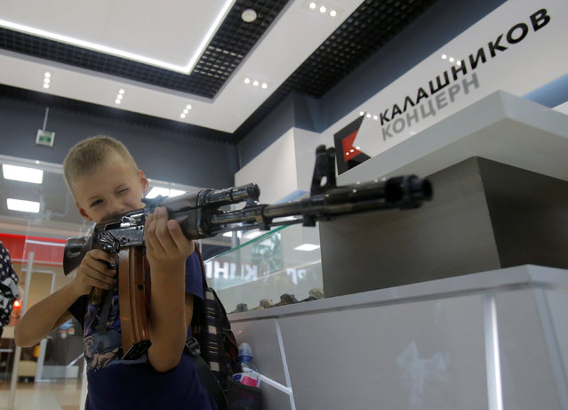 A boy aims with a model AK-47 assault rifle at the newly opened Gunmaker Kalashnikov souvenir store in Moscow's Sheremetyevo airport, Russia, August 22, 2016. (Photo by Maxim Shemetov/Reuters)
