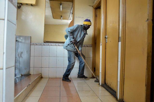 A man cleans public toilets on November 7, 2017 in the Kawangware district of Nairobi, Kenya. (Photo by Simon Maina/AFP Photo)