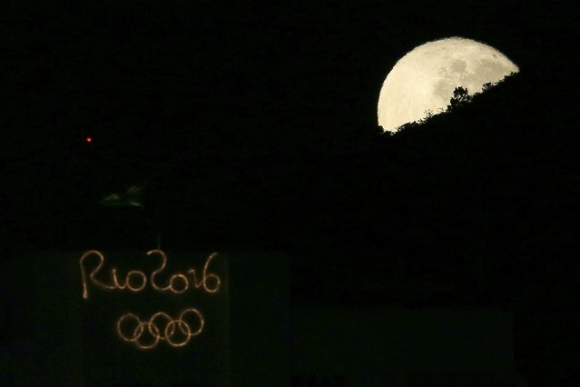 The moon sets behind a hill and a building with an electronic sign for the Rio 2016 Olympics in the Copacabana neighborhood of Rio de Janeiro, August 17, 2016. (Photo by Bruno Kelly/Reuters)