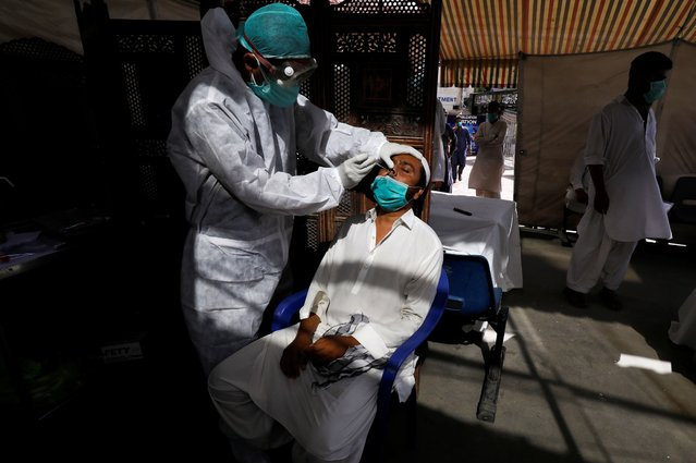 A paramedic wearing protective gear takes a nose-swab sample to be tested for the coronavirus disease (COVID-19), in Karachi, Pakistan on June 27, 2020. (Photo by Akhtar Soomro/Reuters)