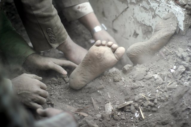 The feet of a child covered in dust are seen as people search for survivors under the rubble of a house destroyed by an air strike at the old quarter of Yemen's capital Sanaa, September 19, 2015. At least ten Yemeni civilians were killed in air strikes by Saudi-led warplanes that targeted this neighborhood, medical sources said on Saturday. (Photo by Mohamed al-Sayaghi/Reuters)