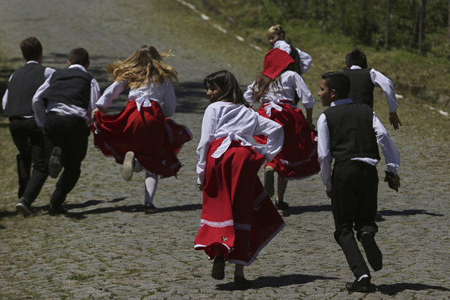"In this November 11, 2017 photo, children dressed in traditional outfits play during the Azorean Culture Festival which celebrates the culture of the Azores, the Portuguese island chain in the mid-Atlantic, in Enseada de Brito, in Brazil's Santa Catarina southern state. ""We have to make sure that our culture always stays alive, not let it die"", said Andre Cordeiro, who leads one of the singing and dancing groups that performed this year. ""We are able to pass it on from generation to generation"". (Photo by Eraldo Peres/AP Photo)"