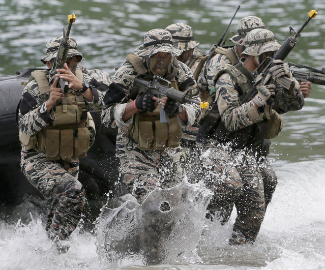 "Philippine Marines from the Naval Special Operations Group (NAVSOG) storm the beach to simulate an ""extraction"" of a kidnapped victim as they kick off a five-day amphibious military exercise at the Philippine Marines training center in Ternate, Cavite province, about 50 miles (80kms) south of Manila, Philippines Thursday, September 24, 2015. (Photo by Bullit Marquez/AP Photo)"