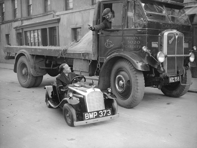 A lorry driver talking to the driver of a midget car in Cardiff, February 1935. (Photo by Fox Photos)
