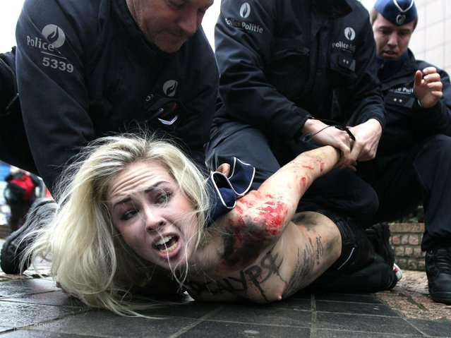 An activist of Ukraine's feminist movement Femen is taken away by the police as she demonstrates by the EU Council building where the EU-Russia summit is taking on December 21, 2012 in Brussels, Belgium. (Photo by Georges Gobet/AFP Photo)