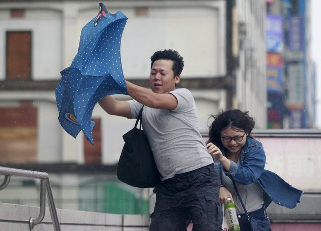 People hold onto their umbrella while walking against strong winds caused by Typhoon Dujuan in Taipei, Taiwan, September 28, 2015. (Photo by Pichi Chuang/Reuters)