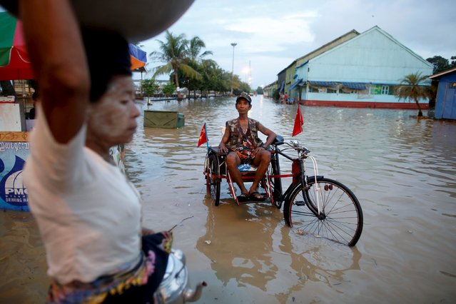 A man sits on his cart which he attached with National League for Democracy (NLD) party flags along a flooded street in Yangon September 30, 2015. Myanmar will hold a general election on November 8. (Photo by Soe Zeya Tun/Reuters)