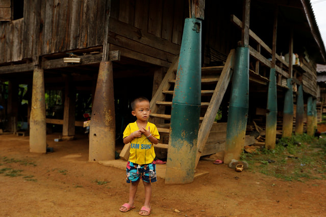 A boy stands in front of a house built on bombs dropped by the U.S. Air Force planes during the Vietnam War, in the village of Ban Napia in Xieng Khouang province, Laos September 3, 2016. (Photo by Jorge Silva/Reuters)