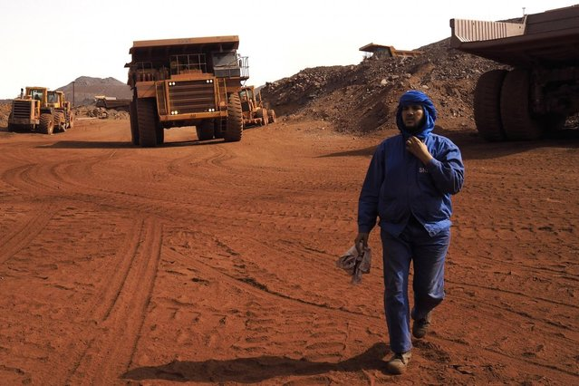 A SNIM truck driver walks in front of trucks at the TO-14 iron ore mine in Zouerate June 23, 2014. SNIM mines black iron ore in the northern town of Zouerate, a remote desert location which nevertheless attracts people from all over the country looking for work. (Photo by Joe Penney/Reuters)