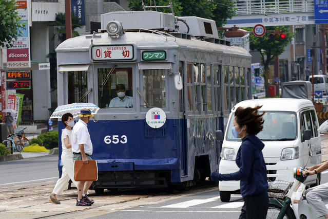 The No. 653 tram, which survived the atomic bomb, runs along the street near the Atomic Bomb Dome to commemorate the 75th anniversary of the U.S. first atomic bombing on the city in Hiroshima, Japan, Thursday, August 6, 2020. (Photo by Eugene Hoshiko/AP Photo)