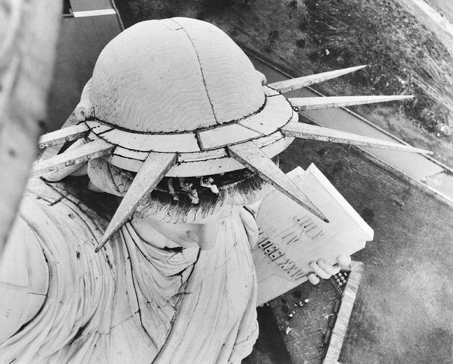 Visitors peek out from under the crown of the Statue of Liberty in New York Harbor, October 26, 1946. (Photo by AP Photo)