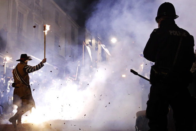 A police watches as participants in costumes hold burning torches during in one of a series of processions during Bonfire night celebrations in Lewes, southern England November 5, 2014. (Photo by Luke MacGregor/Reuters)