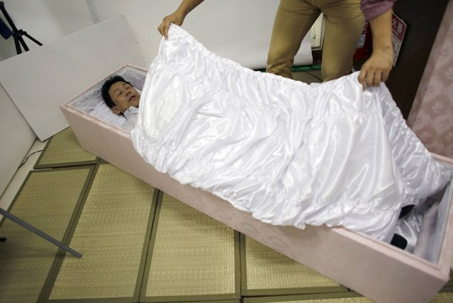 A staff member covers Kazuhiko Kitano with a quilt as he lies in a coffin to test it during an end-life seminar held by Japan's largest retailer Aeon Co in Tokyo October 24, 2014. (Photo by Toru Hanai/Reuters)