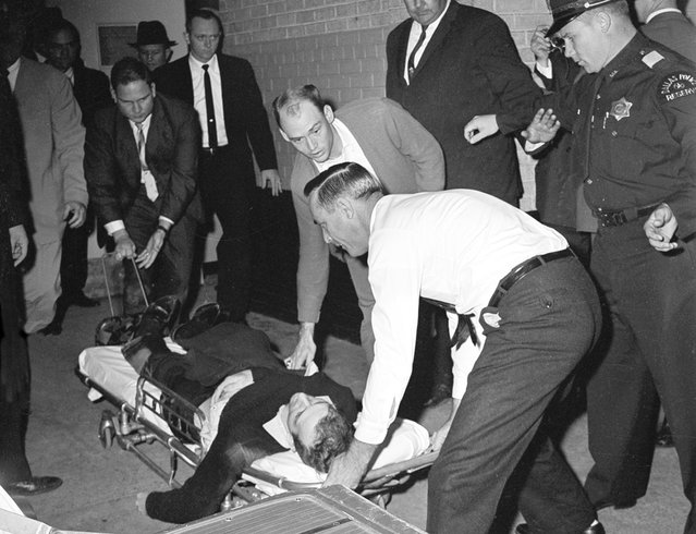 Lee Harvey Oswald, accused assassin of President John F. Kennedy, is placed on a stretcher after moments after being shot in the stomach in Dallas, Texas, on November 24, 1963. Nightclub owner Jack Ruby shot and killed Oswald as the prisoner was being transferred through the underground garage of Dallas police headquarters. (Photo by AP Photo)