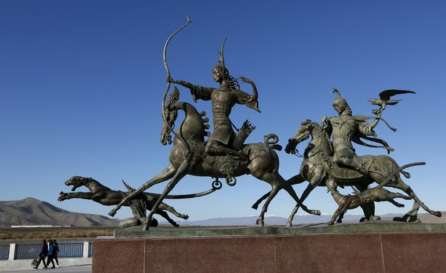 People walk past cast bronze sculptures, created by Russian Buryat artist Dashi Namdakov on an embankment of the Yenisei River in the town of Kyzyl, administrative centre of Tuva region, Southern Siberia, Russia, October 7, 2015. (Photo by Ilya Naymushin/Reuters)