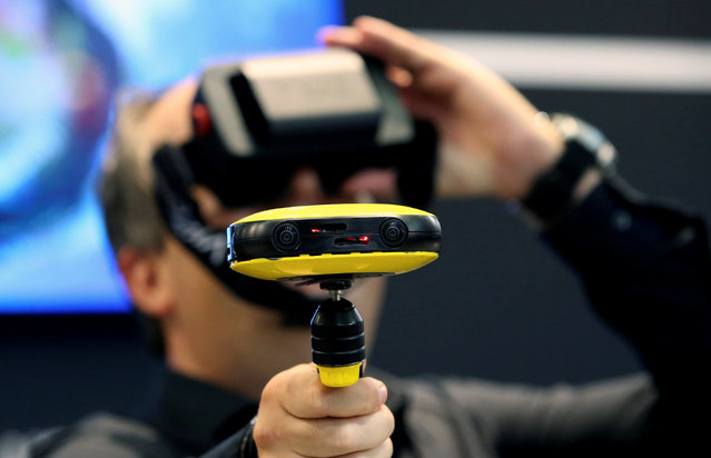 A journalist checks out the Vuze 3D 360 video camera at the Vuze booth on the Photokina, the world's largest fair for imaging in Cologne, Germany, September 20, 2016. (Photo by Fabrizio Bensch/Reuters)