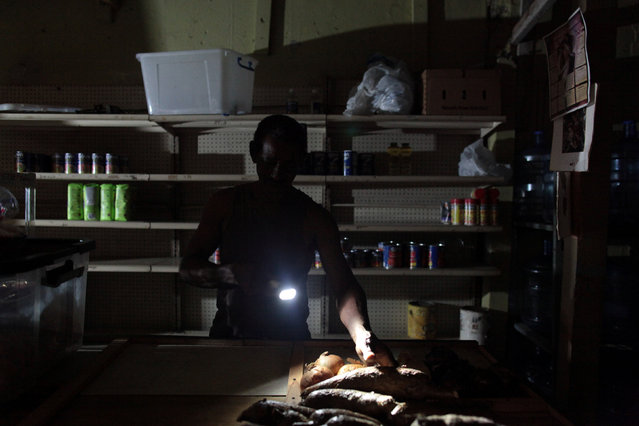 Ramon Ruben points with a flashlight at produce at his store during a power outage that affected several areas in the country, in San Juan, Puerto Rico, September 21, 2016. (Photo by Alvin Baez/Reuters)