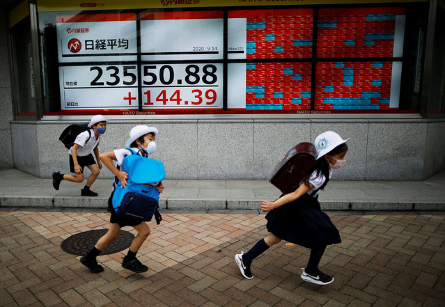 Passersby wearing protective masks run past an electronic board showing Japan's Nikkei average outside a brokerage, amid the coronavirus disease (COVID-19) outbreak, in Tokyo, Japan on September 14, 2020. (Photo by Issei Kato/Reuters)