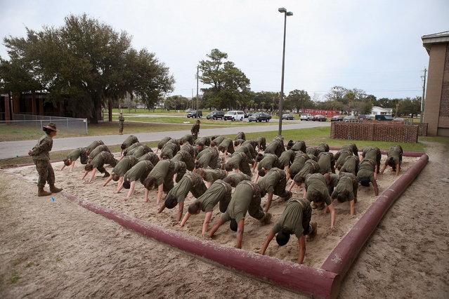 Drill Instructor SSgt. Jennifer Garza of Kerrville, Texas disciplines her Marine recruits with some unscheduled physical training in the sand pit outside their barracks during boot camp February 27, 2013 at MCRD Parris Island, South Carolina. Female enlisted Marines have gone through recruit training at the base since 1949. About 11 percent of female recruits who arrive at the boot camp fail to complete the training, which can be physically and mentally demanding. On January 24, 2013 Secretary of Defense Leon Panetta rescinded an order, which had been in place since 1994, that restricted women from being attached to ground combat units. About six percent of enlisted Marines are female. (Photo by Scott Olson/AFP Photo)