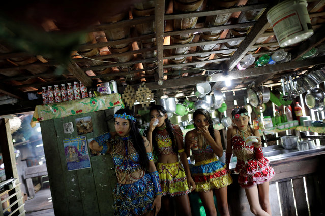 "Members of the ""Bloco Ultima Hora"" group are seen inside a house during Carnival of the Waters, where costumed and colorful boats navigate the river Tentem, around the islands near the city of Cameta, Brazil on February 8, 2018. (Photo by Ueslei Marcelino/Reuters)"