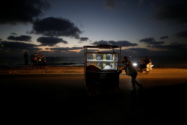 A Palestinian vendor pushes a cart selling sweets on a street, August 18, 2020. Gaza's lone power plant shut down on Tuesday, less than a week after Israel suspended fuel shipments to the Palestinian enclave over the launching of incendiary balloons that have caused brush fires in southern Israel. (Photo by Mohammed Salem/Reuters)