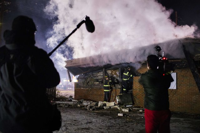 A news crew films as members of the Ferguson Fire Department respond to a flare up in a building that had been destroyed after a night of rioting in Ferguson, Missouri November 25, 2014. (Photo by Lucas Jackson/Reuters)