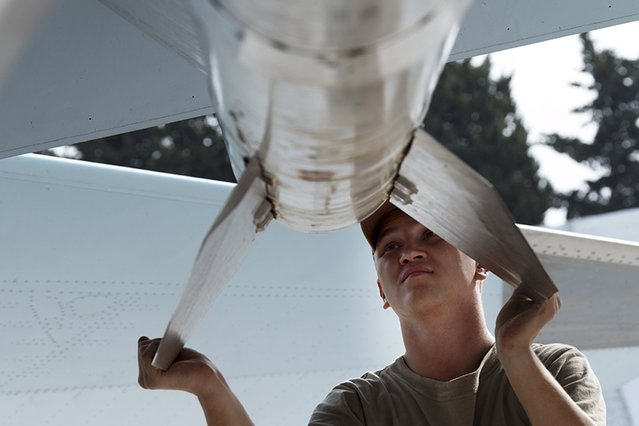A Russian ground staff member loads a Sukhoi Su-30 fighter jet with weapons at the Hmeymim air base near Latakia, Syria, in this handout photograph released by Russia's Defence Ministry October 22, 2015. (Photo by Reuters/Ministry of Defence of the Russian Federation)