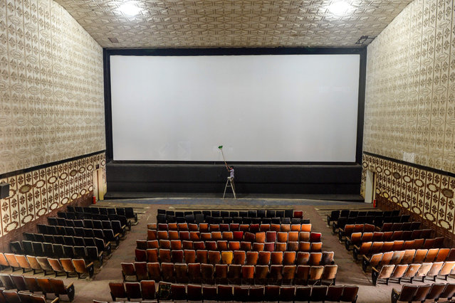 A worker cleans the screen of a cinema hall as part of preparations for a possible reopening after the government eased the lockdown restrictions previously imposed due to the Covid-19 coronavirus, in Chennai on October 8, 2020. (Photo by Arun Sankar/AFP Photo)