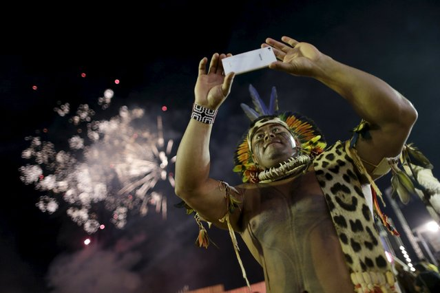 An indigenous man takes photos of fireworks during the first World Games for Indigenous Peoples in Palmas, Brazil, October 24, 2015. (Photo by Ueslei Marcelino/Reuters)