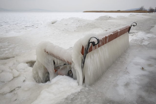 Ice covers a bench on the shore of Lake Balaton in Balatonfenyves, 155 kms southwest of Budapest, Hungary, Monday, February 26, 2018, as extreme cold strengthened by high winds chills most of Hungary. (Photo by Gyorgy Varga/MTI via AP Photo)