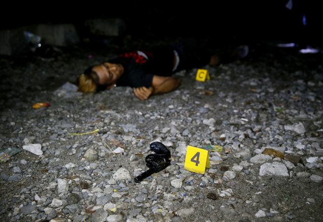 "A pistol is lies near the body of a drug suspect who was killed with two others in an alleged ""buy-bust"" operation before dawn on Friday, September 30, 2016, in Caloocan city, north of Manila, Philippines, in the continuing ""War on Drugs"" campaign of President Rodrigo Duterte. Duterte said he would be ""happy to slaughter"" 3 million addicts. (Photo by Bullit Marquez/AP Photo)"