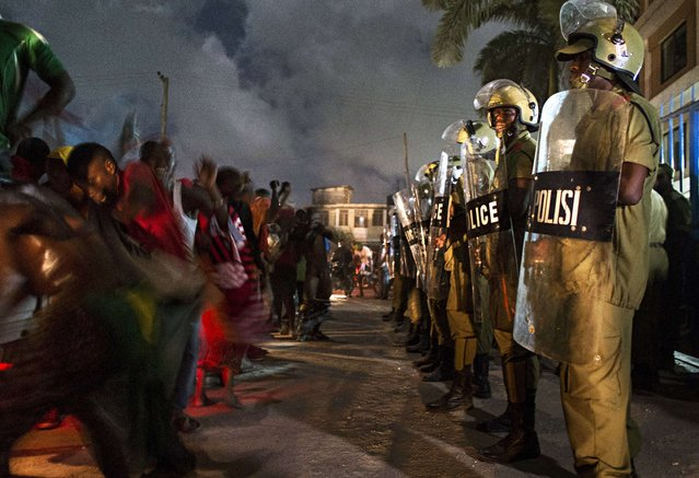 Tanzanian riot police stand guard as people celebrate after the opposition coalition's Civic United Front (CUF) candidate Maulid Mtulia was declared winner of the Kinondoni constituency in Dar es Salaam on October 28, 2015. (Photo by Daniel Hayduk/AFP Photo)