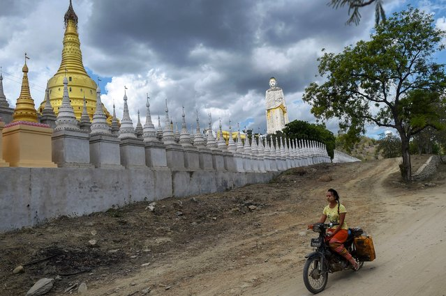 This photo taken on July 25, 2020 shows a girl riding a bike next to Buddhist pagodas in Monywa in the Sagaing region in Myanmar. (Photo by Ye Aung Thu/AFP Photo)
