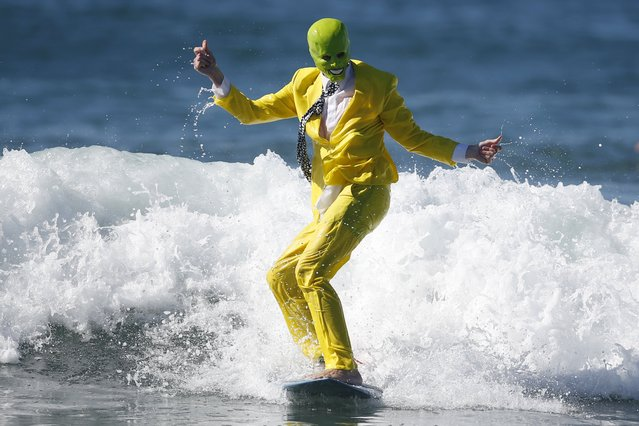 "David Nicholson, 21, surfs as ""The Mask"" during the ZJ Boarding House Haunted Heats Halloween Surf Contest in Santa Monica, California, United States, October 31, 2015. (Photo by Lucy Nicholson/Reuters)"