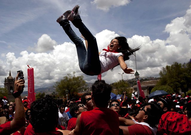 """A reveler is thrown into the air during the """"Jala Toro"""" celebration in Ayacucho, Peru, on March 30, 2013. The Jala Toro is a """"running of the bulls"""" celebration, similar to Spain's Encierro, where bulls are let loose and revelers run around them, except that in Ayacucho's Holy Week, they are led by horsemen called """"Morocuchos"""", the cowboys of the Peruvian Andes. (Photo by Rodrigo Abd/Associated Press)"""