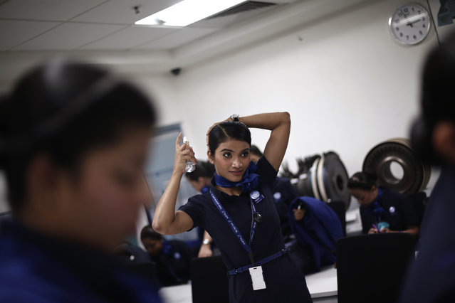A prospective flight attendant uses a hair spray during a training session at Indigo Airlines' Ifly training centre in Gurgaon on the outskirts of New Delhi November 18, 2014. (Photo by Adnan Abidi/Reuters)