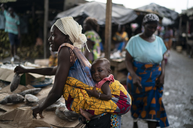 A woman carries her baby as she places fishes for sale at a market in Abobo neighborhood, in the suburbs of Abidjan, Ivory Coast, Sunday, November 1, 2020. (Photo by Leo Correa/AP Photo)