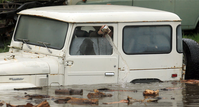 An employee of Mudrak Custom Cruisers bails out a jeep that will be pulled from floodwaters in Sonoma, Calif., Thursday, December 11, 2014. A powerful storm churned down the West Coast Thursday, bringing strong gales and much-needed rain and snow that caused widespread blackouts in Northern California and whiteouts in the Sierra Nevada. (Photo by Kent Porter/AP Photo/The Press Democrat)