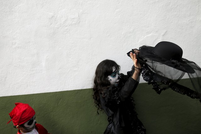 "A girl with her face painted to look like the popular Mexican figure called ""Catrina"", tries to put on her hat as she takes part in the annual Catrina Fest in Mexico City November 1, 2015. (Photo by Carlos Jasso/Reuters)"