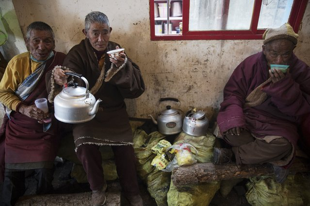 Ethnic Tibetans offer yak butter tea at a Buddhist laymen lodge where thousands gather for daily chanting session during the Utmost Bliss Dharma Assembly, the last of the four Dharma assemblies at Larung Wuming Buddhist Institute in remote Sertar county, Garze Tibetan Autonomous Prefecture, Sichuan province, China October 31, 2015. The traditional tea is made of zanba (roasted Qingke highland barley flour), milk and butter. (Photo by Damir Sagolj/Reuters)