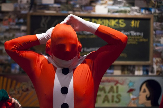 A Santarchy participant adjusts his outfit at Rumba in Seattle, Washington December 13, 2014. (Photo by David Ryder/Reuters)