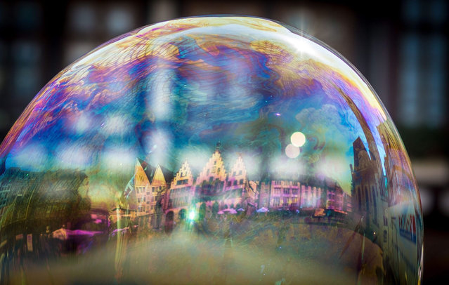 "Frankfurt's city hall, the so-called ""Roemer"" (lit. Roman) is mirrored in a soap bubble in Frankfurt am Main, Germany, 24 July 2015. The medieval building complex in the old part of the city is one of Frankfurt's landmarks and houses the city hall since the 15th century. (Photo by Frank Rumpenhorst/EPA)"