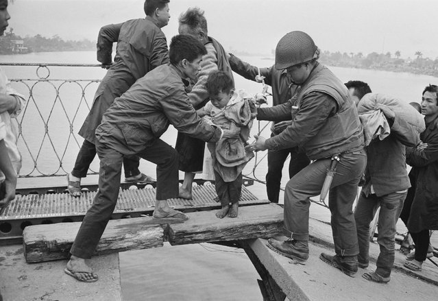Vietnamese refugees crossing the wrecked Trường Tiền Bridge over the Perfume River during the Battle of Huế, Vietnam War, February 1968. (Photo by Terry Fincher/Daily Express/Hulton Archive/Getty Images)